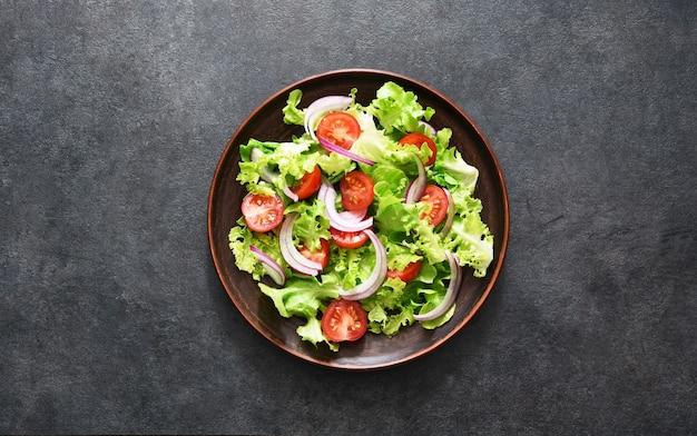 Gemüsesalat mit tomaten, roten zwiebeln und soße auf schwarzer draufsicht
