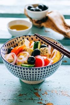 Gemüsesalat und -oliven mit essstäbchen auf hölzernem blauem hintergrund