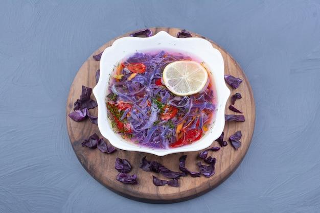 Gemüsesalat und soße mit purpurkohl in einer weißen keramikschale.
