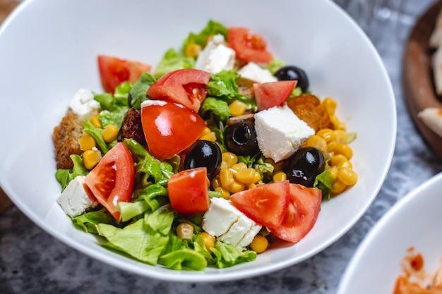 Gemüsesalat von der seite mit weißkäsetomate, schwarzem olivenmaissalat und zwieback