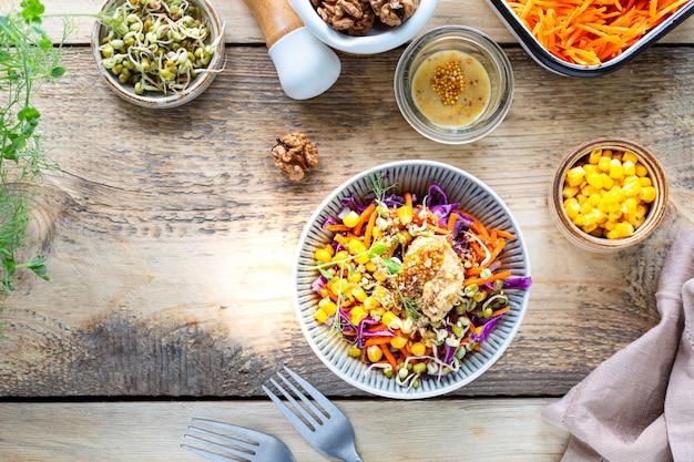 Gemüsesalat von frischem rotkohl mit karotten, zwiebeln, mais, mungosämlingen in einem teller auf hölzernem hintergrund. selektiver fokus. draufsicht. speicherplatz kopieren.