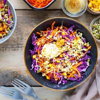 Gemüsesalat von frischem rotkohl mit karotten, zwiebeln, mais, mungosämlingen in einem teller auf hölzernem hintergrund. selektiver fokus. draufsicht.