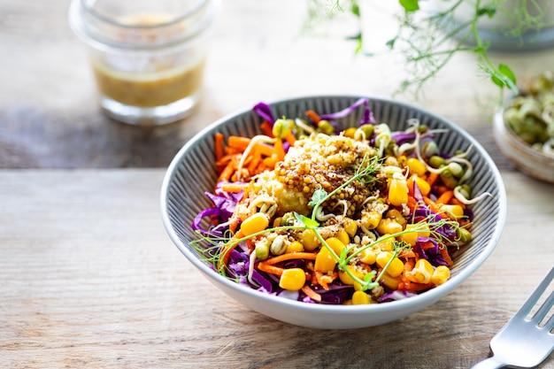 Gemüsesalat von frischem rotkohl mit karotten, zwiebeln, mais, mungosämlingen in einem teller auf hölzernem hintergrund. selektiver fokus. speicherplatz kopieren. horizontal