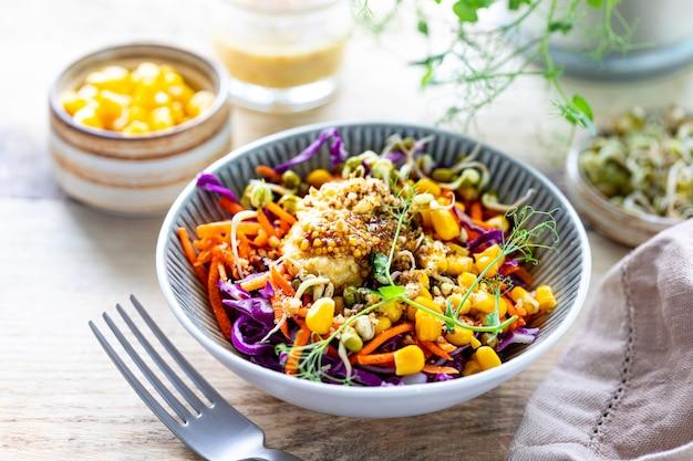 Gemüsesalat von frischem rotkohl mit karotten, zwiebeln, mais, mungosämlingen in einem teller auf hölzernem hintergrund. selektiver fokus.