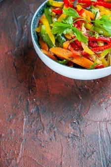 Gemüsesalat von unten in schüssel auf dunkelrotem tisch mit freiem platz