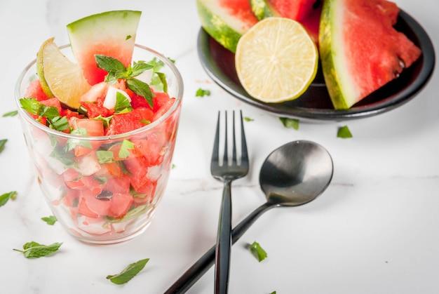 Gemüsesalsasalat mit wassermelone, tomaten, zwiebeln, gemüse, limette in portioniertem glas