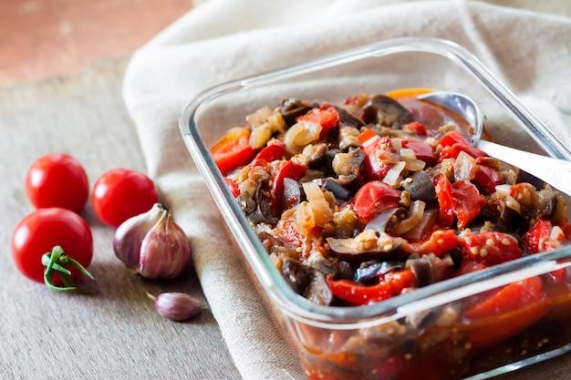 Gemüsesaute mit auberginen, rote paprika und tomaten in glasschüssel
