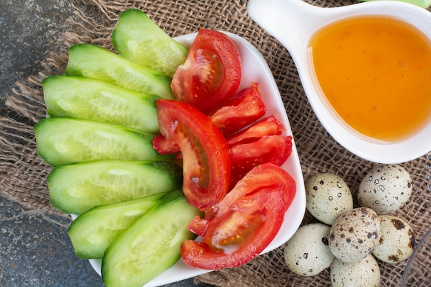 Gemüseschale, wachteleier und honig auf sackleinen.