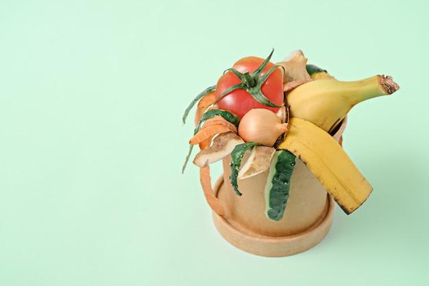 Gemüseschalen im kompostbehälter auf grünem hintergrund, kompostkonzept. kopieren sie platz, nachhaltig und ohne abfall, lebensmittelmüll