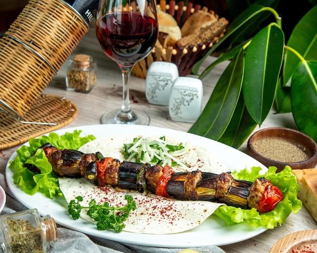 Gemüsespiesse auf fladenbrot mit kräutern und zwiebeln und einem glas rotwein
