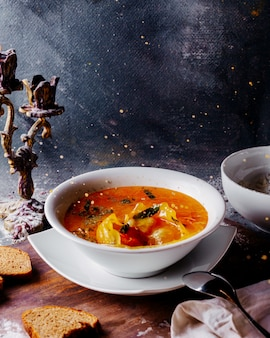 Gemüsesuppe heiß gefärbt mit gemüsestücken innerhalb der weißen platte auf der hellen oberfläche
