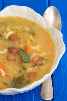 Gemüsesuppe mit bohnen, spinat und nudeln in weißer schüssel