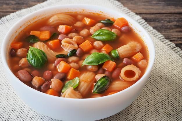 Gemüsesuppe mit bohnen und nudeln, garniert mit grünen basilikumblättern