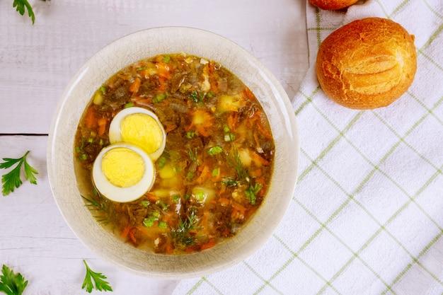 Gemüsesuppe mit ei und knusprigen brötchen