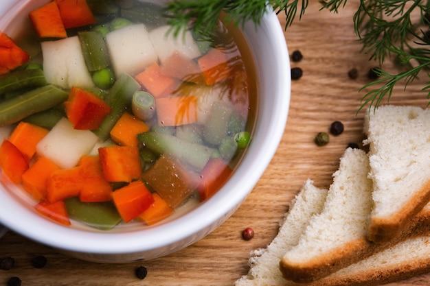Gemüsesuppe mit erbsen, zwiebeln und karotten