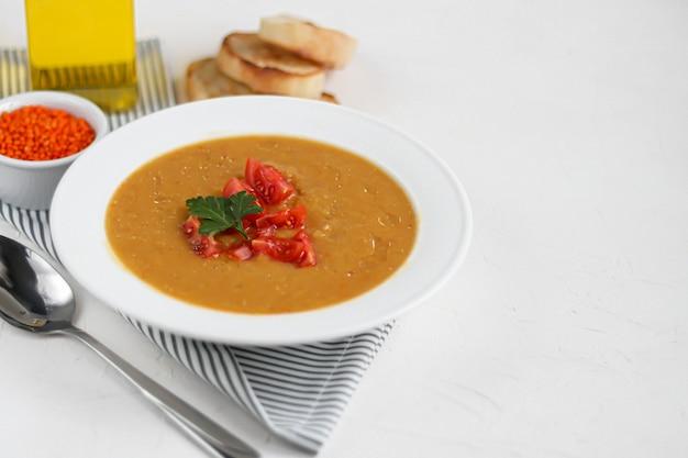 Gemüsesuppe mit linsen auf weißem hintergrund. serviert mit gehackten kirschtomaten und kräutern. in der nähe befinden sich stücke von ciabatta.