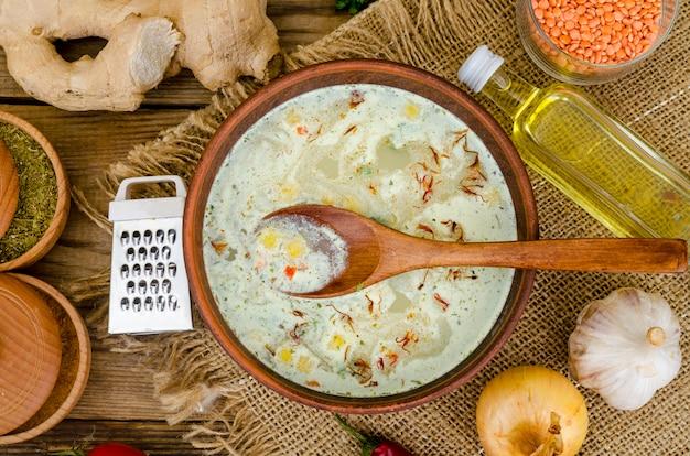Gemüsesuppe mit linsen in der lehmschüssel auf tabelle
