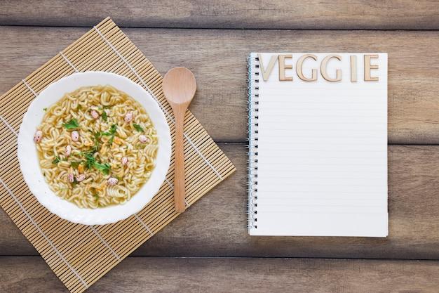 Gemüsesuppe neben gemüse schriftzug auf notebook
