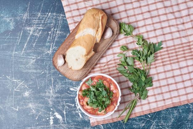 Gemüsesuppe serviert mit baguettebrot.