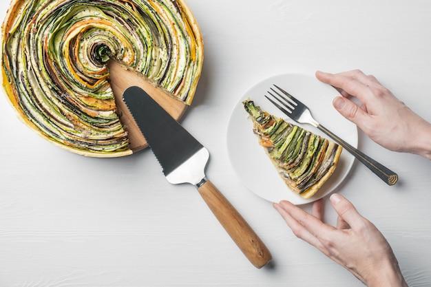 Gemüsetorte der traditionellen französischen ratatouille auf einem weißen hölzernen hintergrund mit herausgeschnittener scheibe