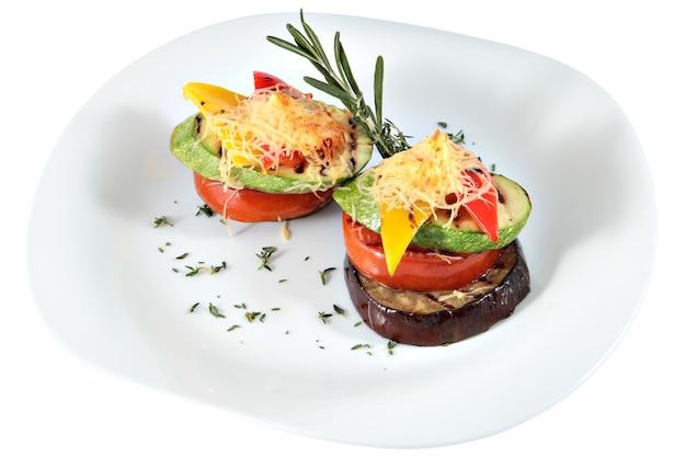 Gemüseturm auf weißer keramikplatte, gebackenes gemüse-mark, aubergine, tomate, parpika isoliert auf weiß.