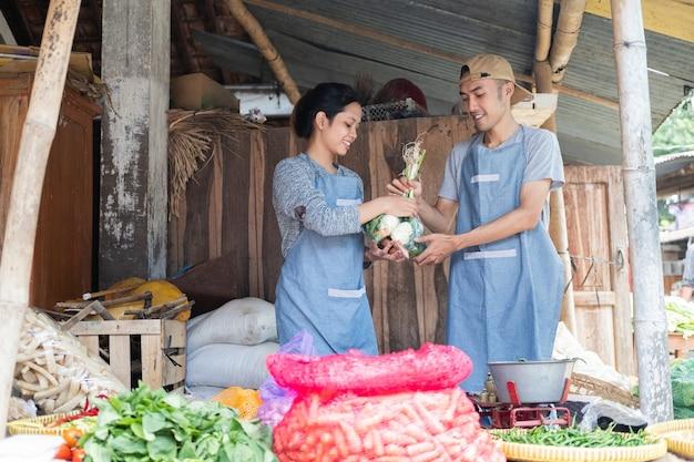 Gemüseverkäufer, der eine schürze trägt, trägt gemüse an einem gemüsestand