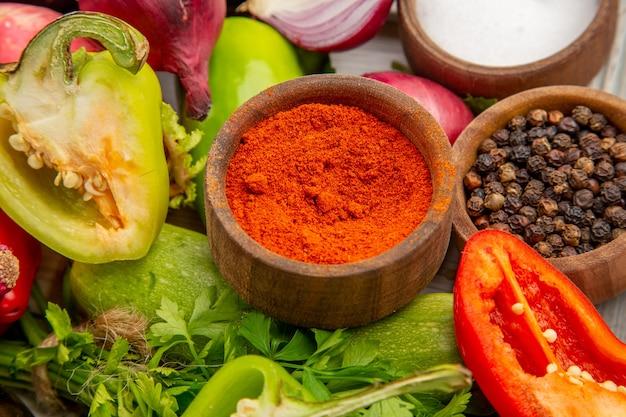 Gemüsezusammensetzung der vorderansicht mit grüns und gewürzen auf weißem hintergrundfarbfotomahlzeit-reifer gesunder lebenssalat