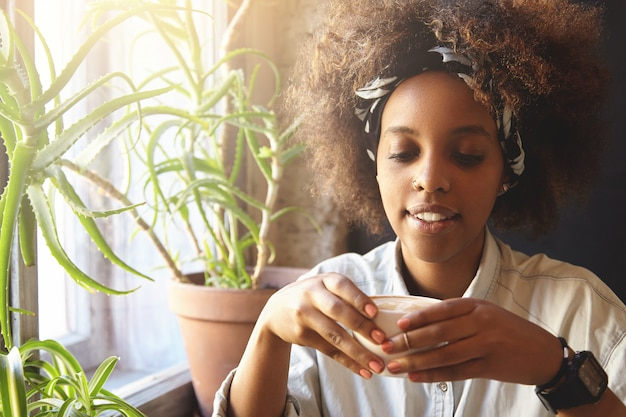 Gemütliche aufnahme eines afrikanischen hipster-mädchens, das ein kopftuch und einen ring in der nase trägt, eine tasse kaffee oder tee hält und am wintermorgen ein heißes getränk trinkt, während es alleine in einer schönen cafeteria oder in ihrer küche zu hause sitzt