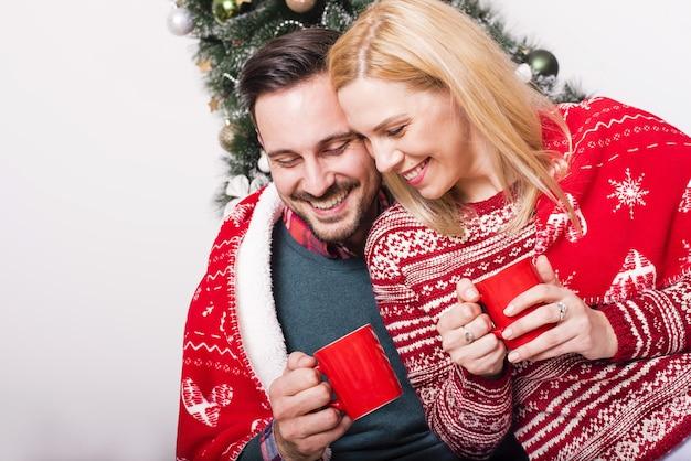 Gemütliche aufnahme eines glücklichen paares, das heißen tee auf dem hintergrund des weihnachtsbaums trinkt?