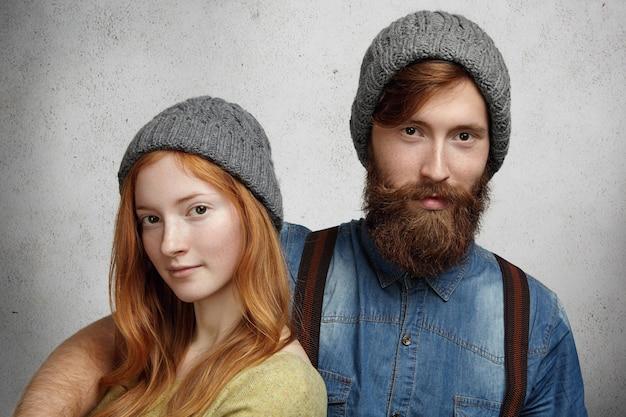 Gemütliche aufnahme von zwei kaukasischen modellen, die graue strickmützen tragen, die zusammen aufwerfen