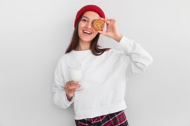 Gemütliche frau des mittleren schusses mit hut, der kekse und milch isst