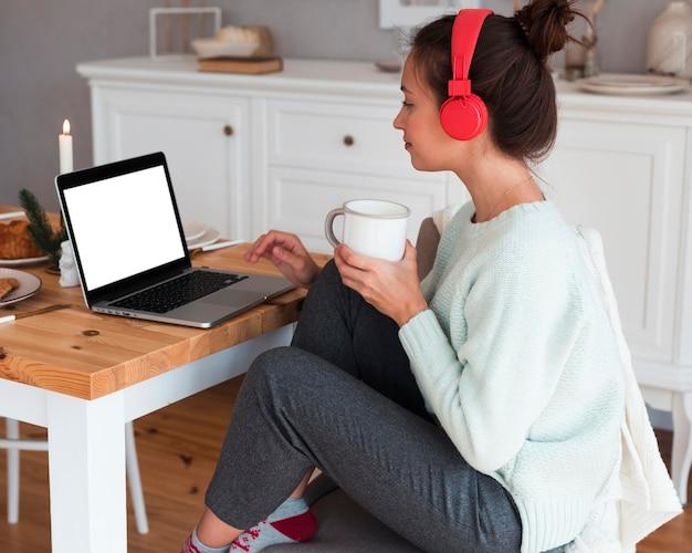 Gemütliche frau, die becher hält und laptop benutzt
