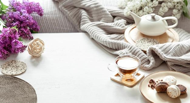 Gemütliche frühlingszusammensetzung mit einer tasse tee, einer teekanne, französischen makronen, lila farbe auf einem leicht verschwommenen tisch.