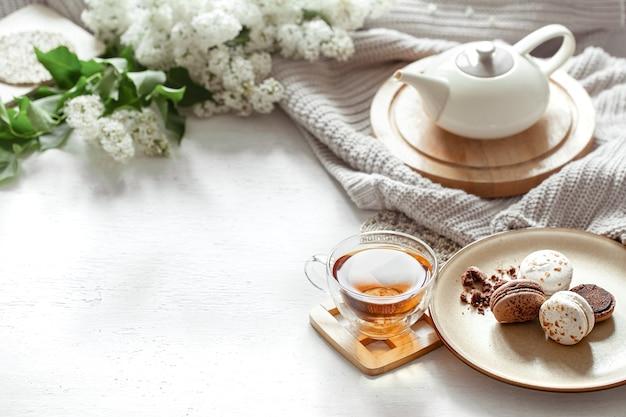 Gemütliche frühlingszusammensetzung mit einer tasse tee, einer teekanne, französischen makronen, lila farbe