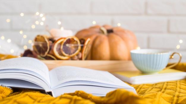 Gemütliche, gemütliche ruhe an einem freien herbsttag - lesen zwischen decken bei einer tasse kaffee
