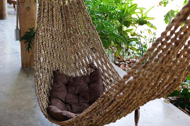 Gemütliche hängemattenwiege zum entspannen auf der terrasse in der nähe des gartens