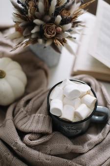 Gemütliche heimherbstdekoration mit einer tasse kaffeebuch kürbisblüten und plaid