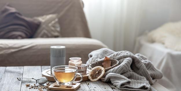 Gemütliche herbstkomposition mit einer tasse tee, kerzen und einem gestrickten element auf einem unscharfen hintergrund des rauminneren.