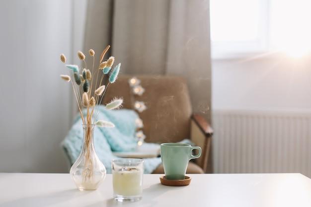 Gemütliche inneneinrichtung mit tasse kaffee, kerze und einer vase mit blumen auf einem couchtisch