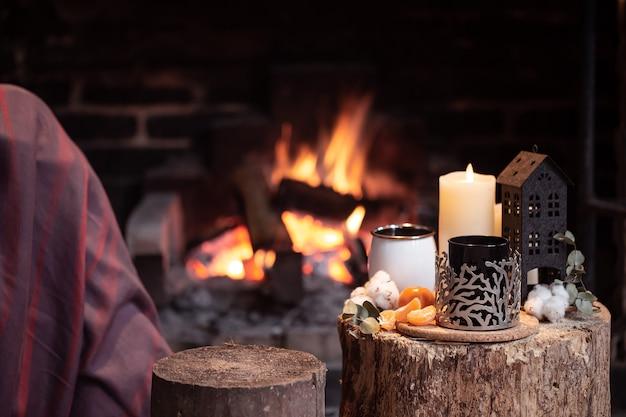 Gemütliche komposition mit einer tasse, einer kerze und mandarinen auf einem unscharfen hintergrund eines brennenden kaminkopierraums.
