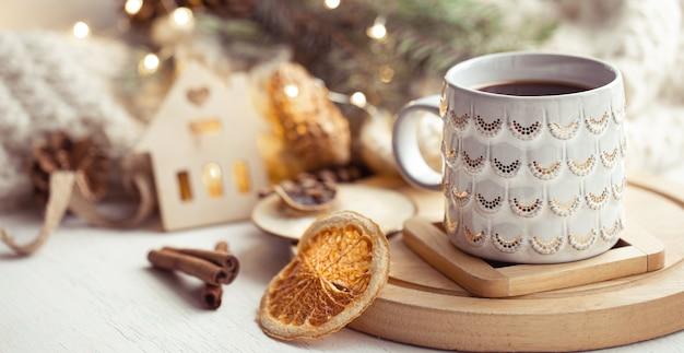 Gemütliche komposition mit einer weihnachtsschale mit einem heißen getränk und zimt auf einem unscharfen hintergrund. home winter gemütlichkeitskonzept.