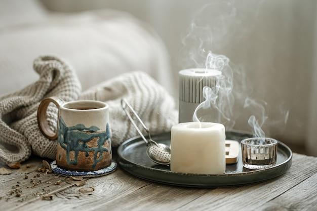 Gemütliche komposition mit keramiktasse, kerzen und einem gestrickten element auf unscharfem hintergrund. Kostenlose Fotos