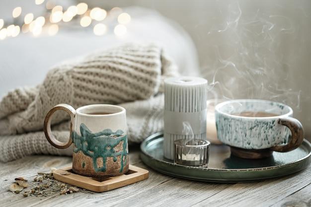 Gemütliche komposition mit keramiktassen und kerzen auf verschwommenem hintergrund mit bokeh.