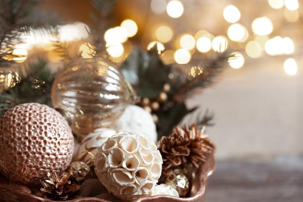 Gemütliche komposition mit spielzeugen auf einem weihnachtsbaum auf einem unscharfen hintergrund mit bokeh. dekor und weihnachtsstimmung konzept.