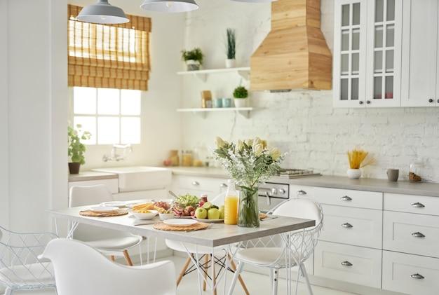 Gemütliche küche, modernes helles weißes kücheninterieur mit hölzernen und weißen details vase mit blumen