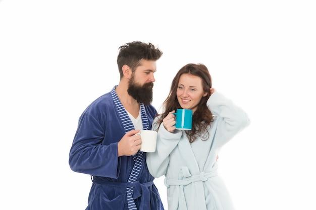 Gemütliche momente. batch brew wird über den kaffee gegossen, der mit hilfe der maschine hergestellt wurde. kaffeespezialitäten einfach zubereiten. paare in häuslicher kleidung genießen morgenkaffee. bademäntel für mann und frau trinken kaffee.