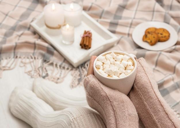 Gemütliche person, die becher mit heißem kakao und marshmallows hält