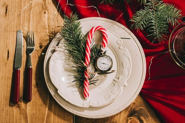 Gemütliche schöne neujahrstischdekoration mit einer roten tischdecke, antiken utensilien und einer vintage-uhr auf dem tisch.