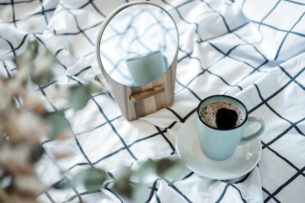 Gemütliche stimmung am morgen. kaffee im bett. eine tasse schwarzen kaffee im bett auf weiß karierter decke. selektiver fokus