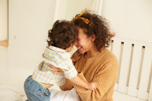 Gemütliche szene einer glücklichen, überglücklichen, jungen, lockigen mutter, die einen kleinen sohn in ihre arme kuschelt, sich im schlafzimmer verbindet, die mutterschaft genießt und eine tiefe verbindung zu ihrem kleinkind hat. liebe und glück